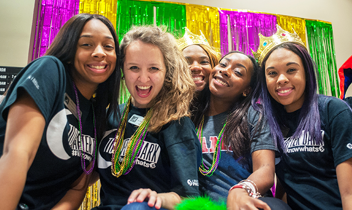 Students smile at camera while at a Tide After Dark Mardi Gras event