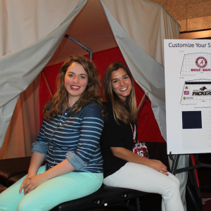 Susan Fant (left) and one of her graduate students, Liza Bollinger (right) worked with Kinematic Sports to effectively market the company's medical privacy tent at the Alabama coach's clinic. Fant said these types of opportunities give her students the real, hands-on experience they need to succeed in their future careers.